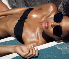 Dark tan woman wearing black sunglasses and a black bikini top