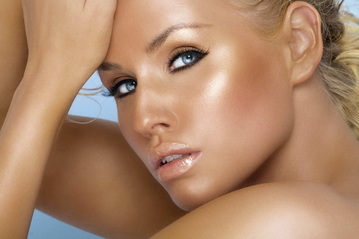 close up image of a beautiful blue-eyed tanned woman with makeup to enhance her tan, she looks like