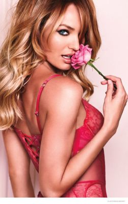upper half of the body of a blond in a red bra holding a pink rose